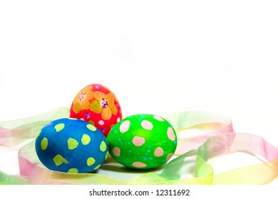 Three hand painted Easter eggs with ribbon on a white background.