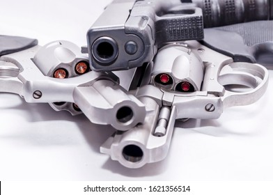Three handguns, two revolvers, a 357 magnum and a 44spl along with a black 9mm pistol on a white background