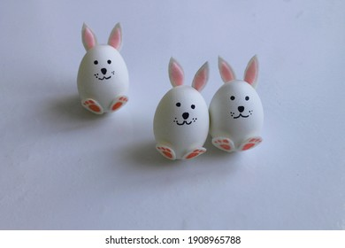 Three handmade bunnies are made of a chicken egg. Cardboard ears and paws. Easter holiday concept.