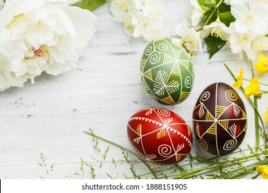 Three handmade Easter eggs decorated with wax-resist dyeing technique. Ukrainian pysanka on white shabby wooden background with empty space for text