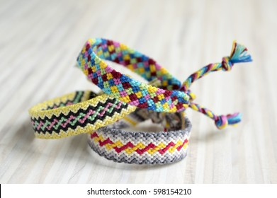 Three handmade homemade natural woven bracelets of friendship on white wooden table rainbow colors, checkered pattern