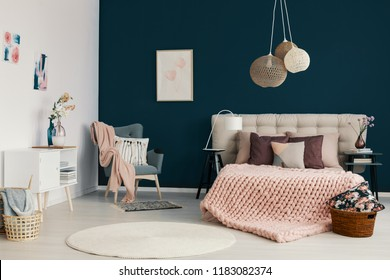Three handmade lamps hanging above bed with soft bedhead in the real photo of white and blue bedroom interior