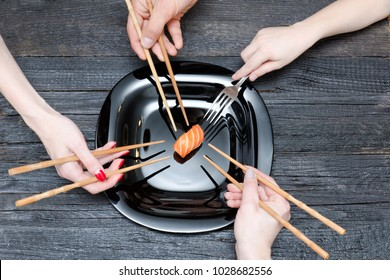 Three hands with chopsticks, one with fork and sushi. Black wooden background. Top view