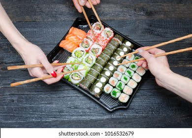 Three hands with chopsticks and sushi set. Black wooden background. Top view