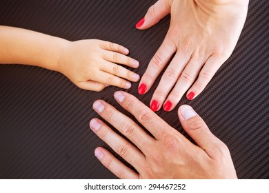 Three hands of the family- baby, mother and father. Concept of family, unity, protection, support and happiness.