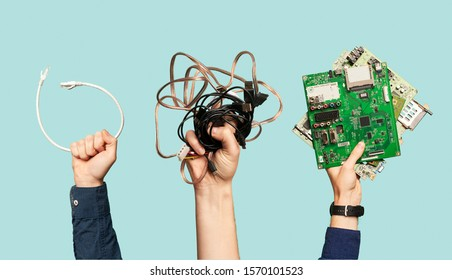 Three hands hold electrical waste on blank blue background.