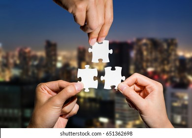 three hands holding piece of jigsaw puzzle on cityscape background. business partnership concept. business matching.