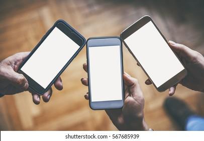 Three hands holding smart phones