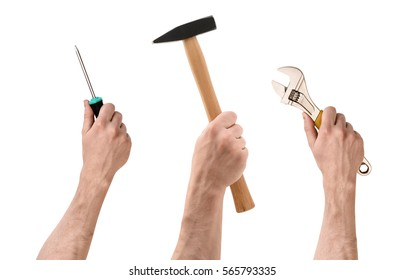 Three hands with screwdriver, hammer, and wrench on white background. Handmade and DYI. Manual labor. Building and repair.