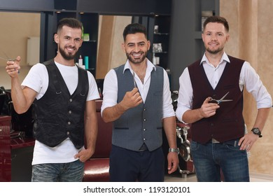 Three handsome barbers posing and smiling. Bearded hairdressers standing in barbershop and holding scissors in hands. Professional confident masters wearing white shirts and vests.