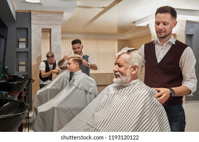 Three handsome barbers styling clients haircut in barbershop. Men wearing in striped coiffure capes. Professional hairstylists concentrated on cutting and grooming hair.