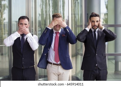 three handsome businessmen as the three wise monkeys