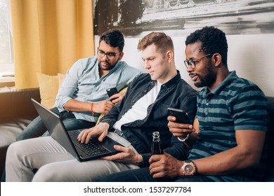 Three handsome men in casual clothes relaxing in living room, watching online video or sport matches on laptop together sitting on sofa at home. Friends, technology, leisure concept.