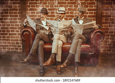 Three handsome men in elegant suits sit on a leather sofa, smoke cigars and read newspapers. Newspaper editorial office. Retro style. Men's fashion. - Shutterstock ID 1892147689