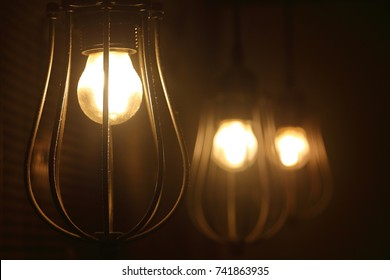 Three hanging antique style incandescent lamps shining a golden yellow light in a dark room. The bulbs are protected by a cage of steel bars.