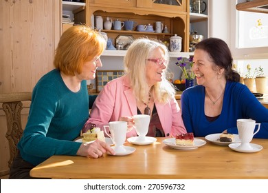 Three Happy Adult Female Friends Having Cups of Tea or Coffee and Slices of Cakes at the Wooden Table While Talking Funny Moments.