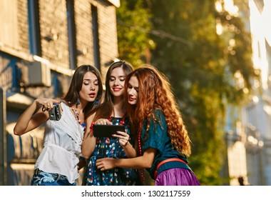 Three happy attractive women looking photos on tablet