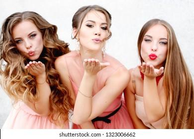 Three happy beautiful brides together. Party time of stylish women group in elegant dress celebrating birthday, having fun, wedding, prom.