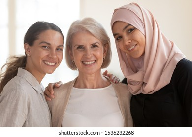 Three happy beautiful diverse two generation women young asian muslim woman wear hijab and caucasian older mature female multicultural ladies bonding standing together looking at camera, portrait