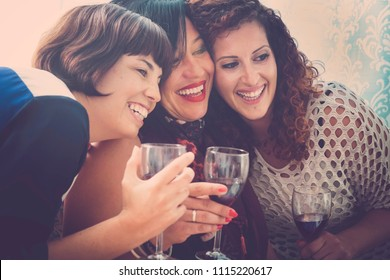 three happy and beautiful females friends have fun together at home drinking some red wine and enjoying the leisure and tie friendship. relationship with friends concept in vintage colors