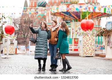 Three Happy Beautiful girlfriends take pictures on the background of the red square in the center of Moscow