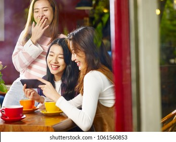 three happy beautiful young asian women sitting at table chatting talking laughing playing with cellphone in coffee shop or tea house, shot through window glass.