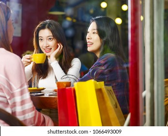 three happy beautiful young asian women sitting at table chatting talking in coffee shop or tea house after shopping, shot through window glass.