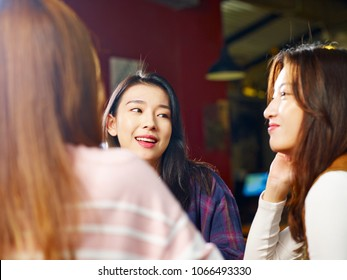 three happy beautiful young asian women sitting at table chatting talking in coffee shop or tea house.
