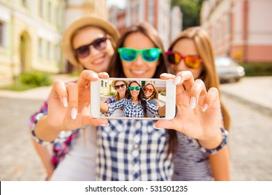 Three happy best girlfriends in glasses making selfie on smartphone.