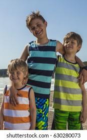 Three happy boys hugging on the beach. Summer vacation.