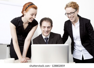 Three happy business colleagues, a business man and two women, looking at the screen of a laptop together and smiling in amusement