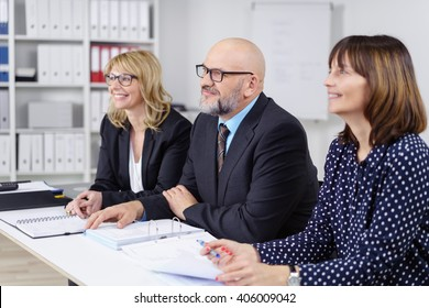Three happy business co-workers in a meeting sitting at a table at the office listening to a presentation with friendly pleased smiles, middle-aged man and two women