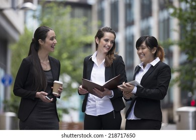 Three Happy Business women outside the office talking to each other.
