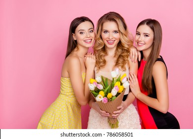 Three happy charming, pretty girls in elegant dresses with hairstyle celebrating women's day, eight-march, holding bouquet of colorful tulips, standing over pink background