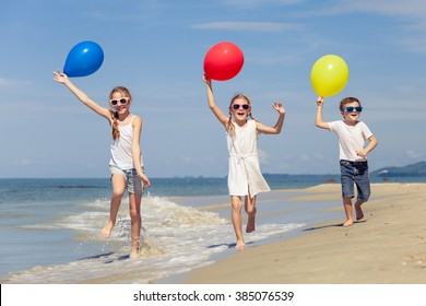 Three happy children with balloons playing on the beach at the day time. Concept of happy friendly family.