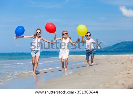 Three Happy Children With Balloons Running On The Beach At The Day Time Concept Of