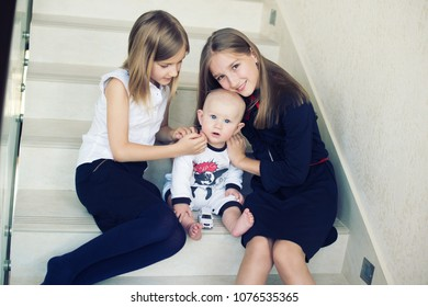 Three happy children in family playing together at home. Older sisters holding young infant brother baby on hands.