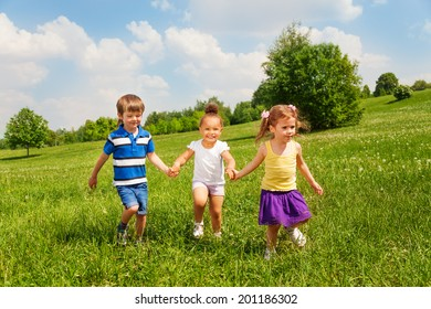 Three happy children holding hands and playing