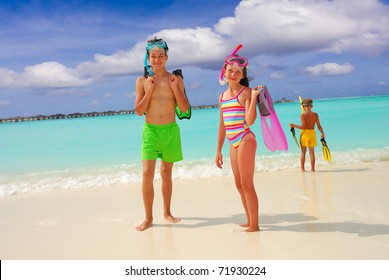 Three happy children on tropical beach with snorkeling equipment, sea in background.
