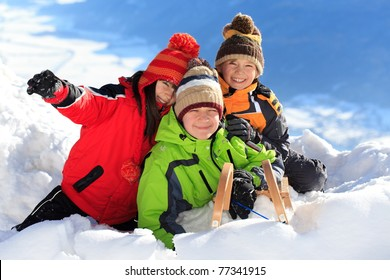 Three happy children playing on snowy mountain.