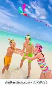 Three happy children with snorkels flying kite in sea, blue sky and cloudscape background.