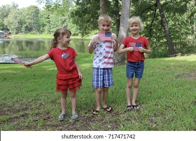 Three happy children waving American flag in patriotic clothes whilst celebration the Fourth of July