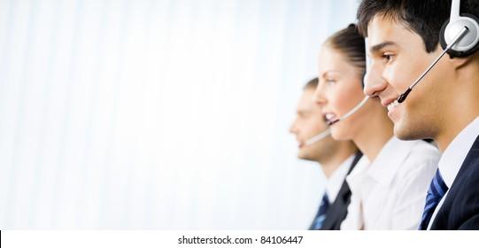 Three happy customer support phone operators at office