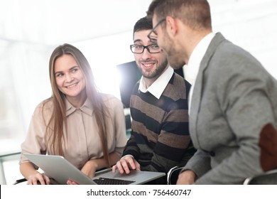 Three happy employees working on line with a tablet