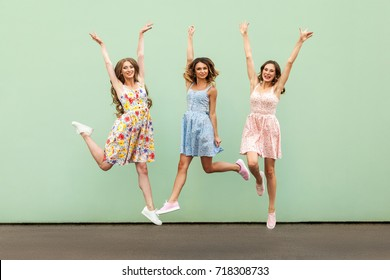 Three happy excited young adult women in casual dresses celebrate victory and jumping over green background. Outdoor