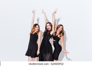 Three happy excited young women dancing with raised hands and showing peace signs over white background