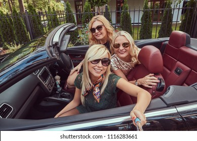 Three happy fashionable female friends take a selfie photo in luxury cabriolet car, during their trip vacation.