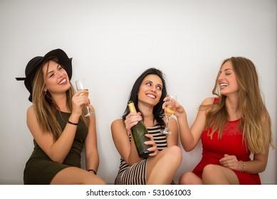 Three happy female friends enjoying drinks.