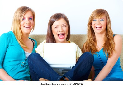 Three happy friends beautiful girls sitting on sofa in home with laptop computer