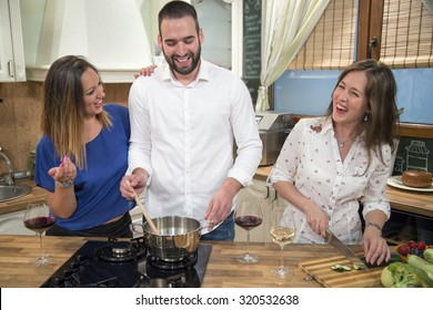 Three happy friends cooking and having fun in the kitchen. They are preparing food together and laughing. Two girls and man having fun while preparing food.